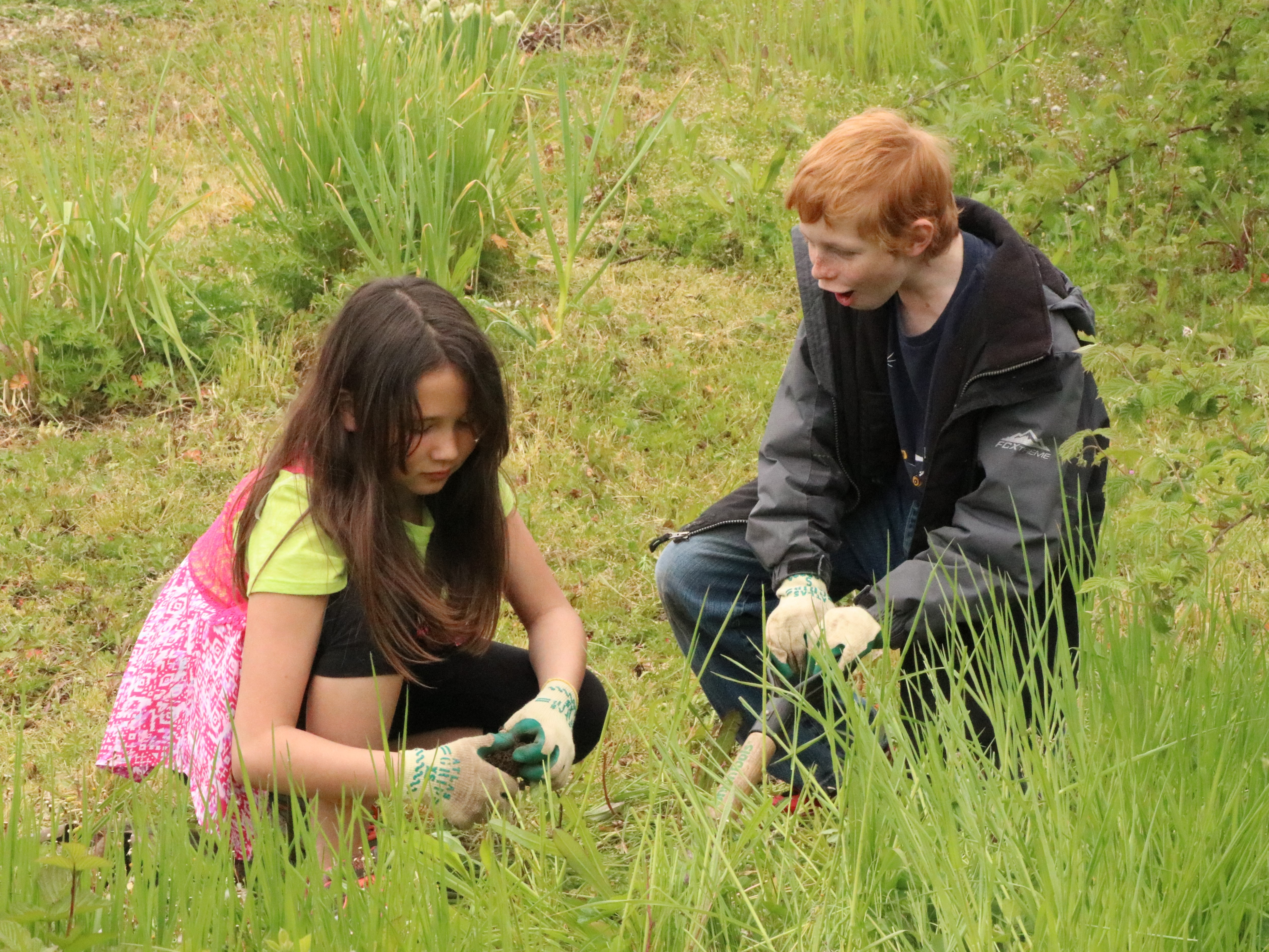 Fifth-graders Ava Soderholm and Nicky Brett work together in the Cascades School garden.