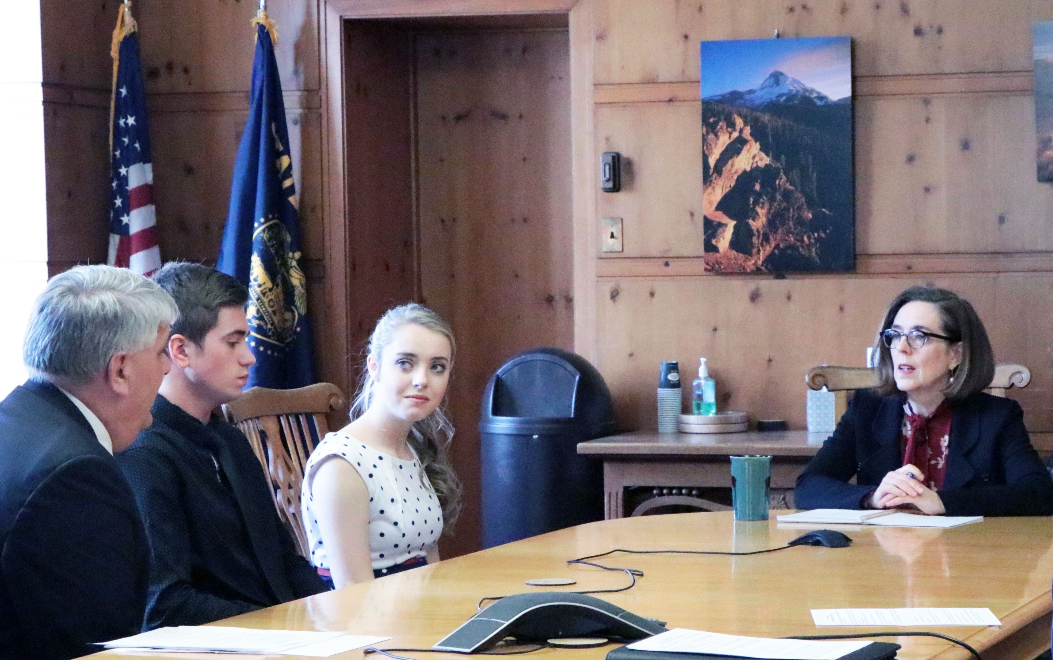 Coquille School District Superintendent Tim Sweeney (from left) and high school juniors Lucas Dane and Sammie Huffman share the school-level impacts of State School Fund decisions with Gov. Kate Brown on Tuesday. (Photo by Rachel Baker, OSBA)