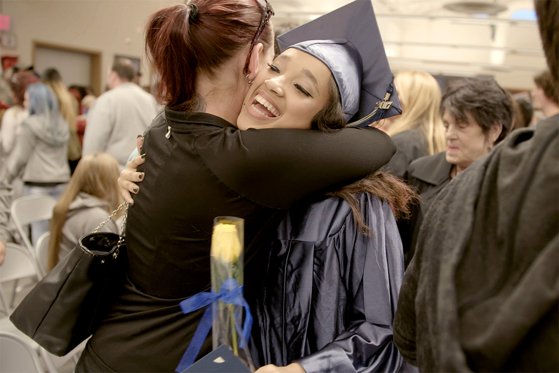 mother and daughter hugging after graduation