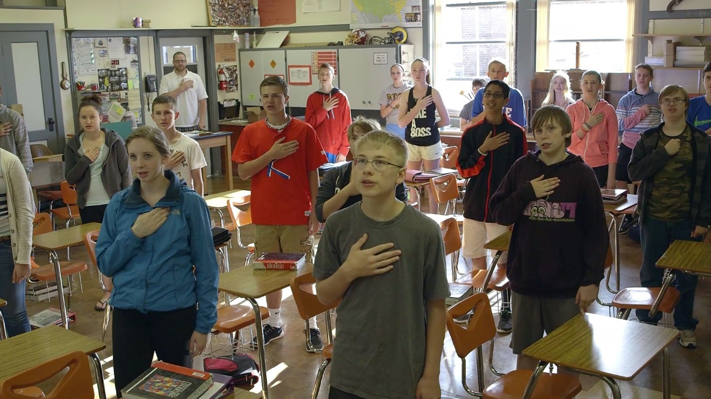 Students pledging allegiance in class